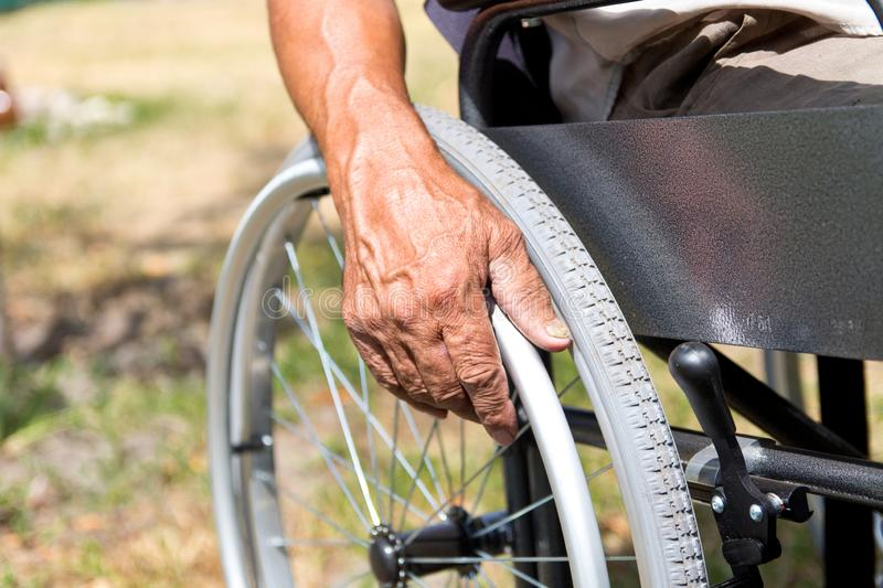 A disabled man is sitting in a wheelchair ,Holds his hands on the wheel. Handicap people Concept. Medical, mature, elderly, disability, happy, sick stock images