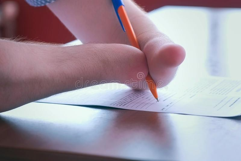 Disabled man with two amputated stump hands signs documents makes paper work. royalty free stock photo