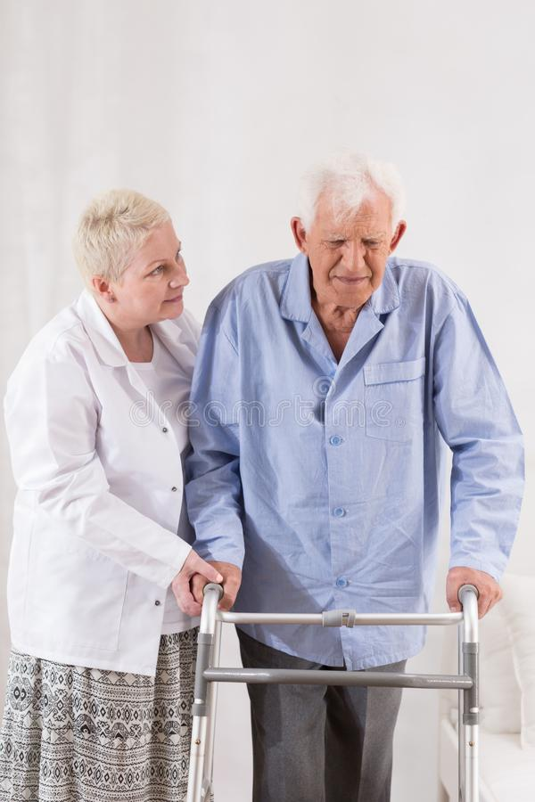 Disabled man using a walking frame stock photography