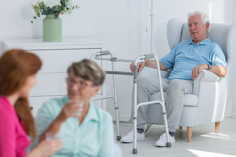 Disabled man with walker. Disabled men with walker sitting in armchair stock image