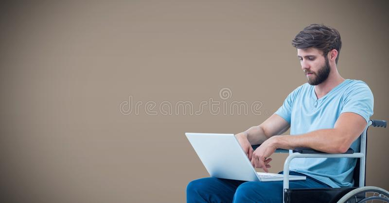Disabled man in wheelchair on laptop with brown background royalty free stock photo