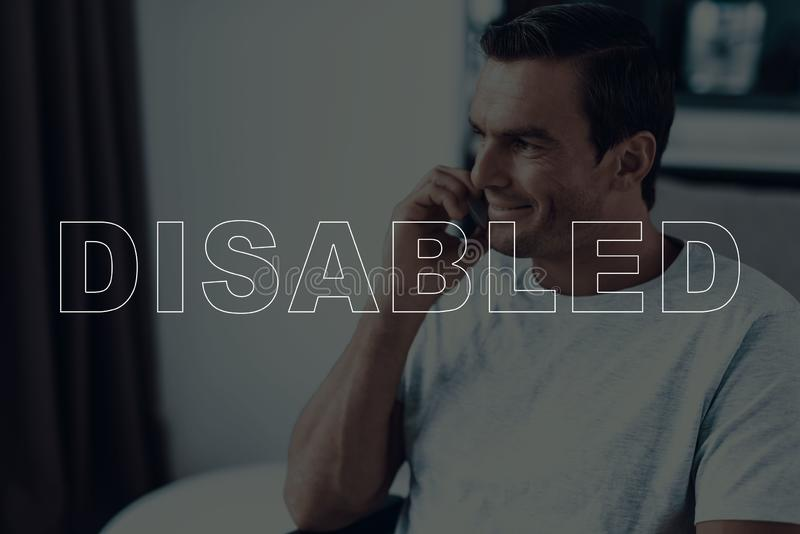 Disabled man in a wheelchair talking on smartphone stock images