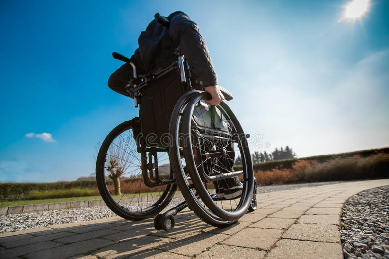 Disabled man in wheelchar driving in the sun royalty free stock photo