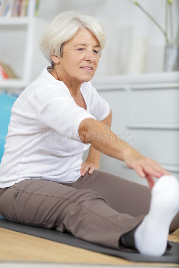 Disabled mature woman performing stretching exercise royalty free stock images