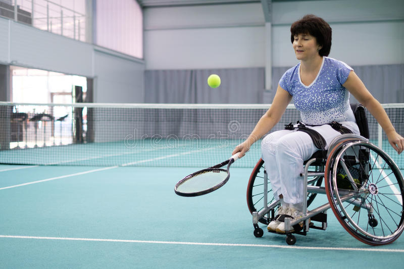 Disabled mature woman on wheelchair playing tennis on tennis court stock photos