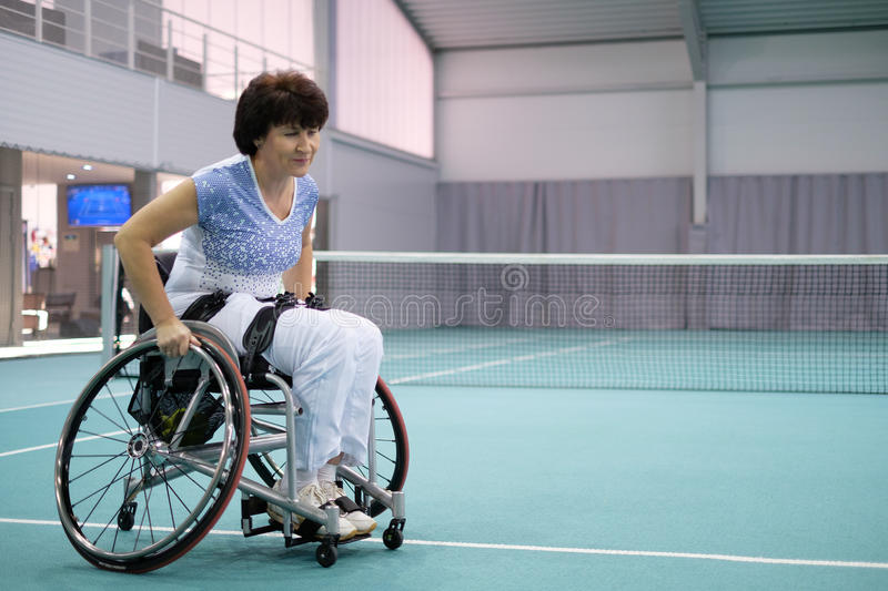 Disabled mature woman on wheelchair on tennis court royalty free stock photos