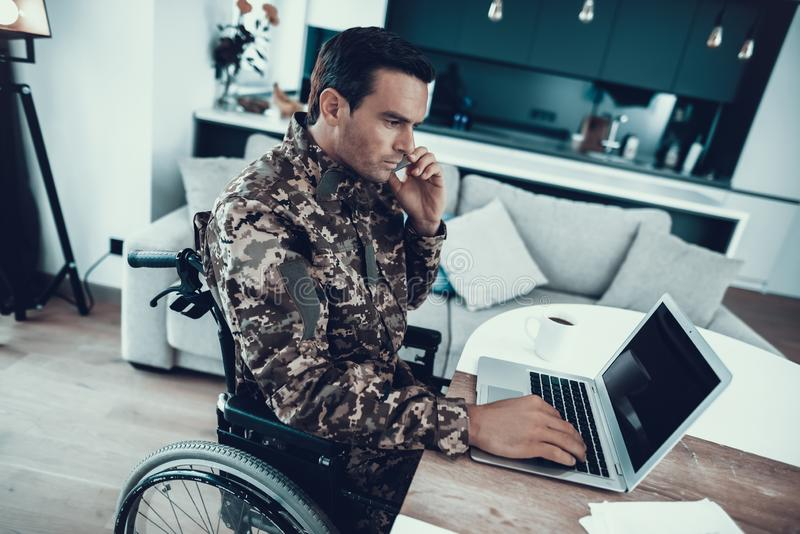 Disabled Military Works on Laptop and Telephones. Military in Wheelchair Work on Laptop and Telephones. Serious Handicapped Man in Uniform Sits at Desk and Uses stock photography