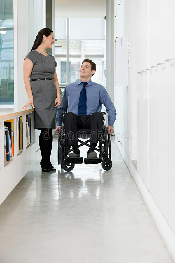 Disabled office worker with colleague stock image