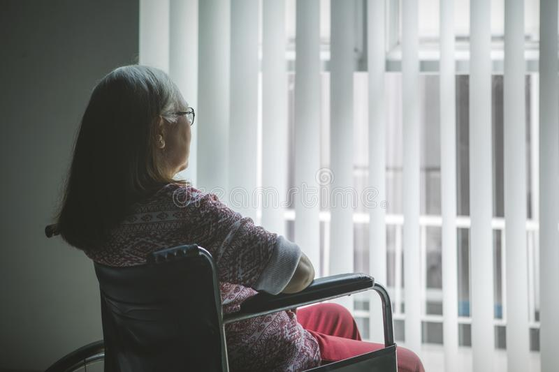 Disabled old woman looking out the window stock photography