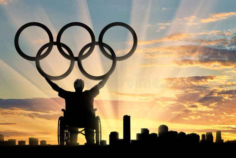 Disabled paralympic keep olympic rings sunset city. Paralympic wheelchair raised his hands and keep olympic rings sunset city. Concept sports and willpower stock photography