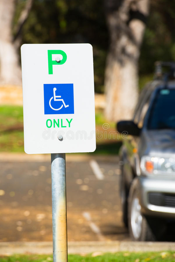 Disabled Parking sign reservation outdoor. Close up parking sign reservation for disabled driver or person, wheelchair symbol on blue, car in blurred background stock photography