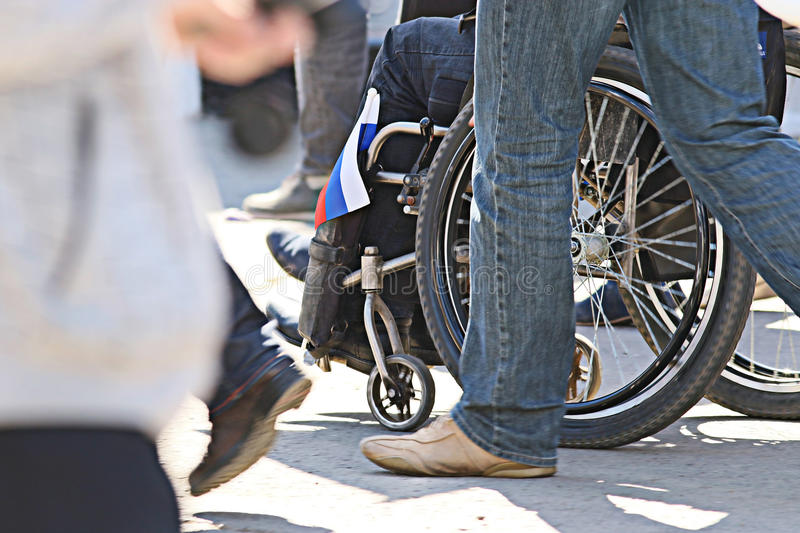 Disabled people in the crowd. Feet stock image