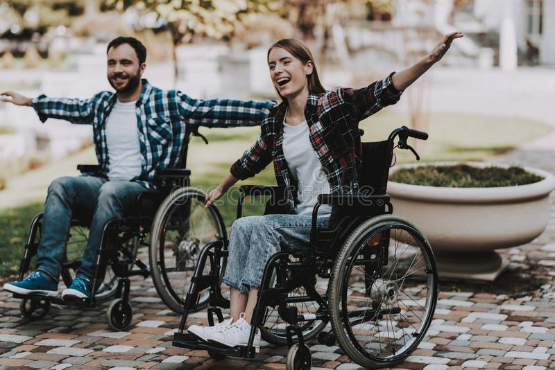 Disabled People on Wheelchairs Have Fun in Park. Disabled Young Man. Woman on Wheelchair. Relaxing in Summer Park. Fun in Summer Park. Recovery and Healthcare stock photos