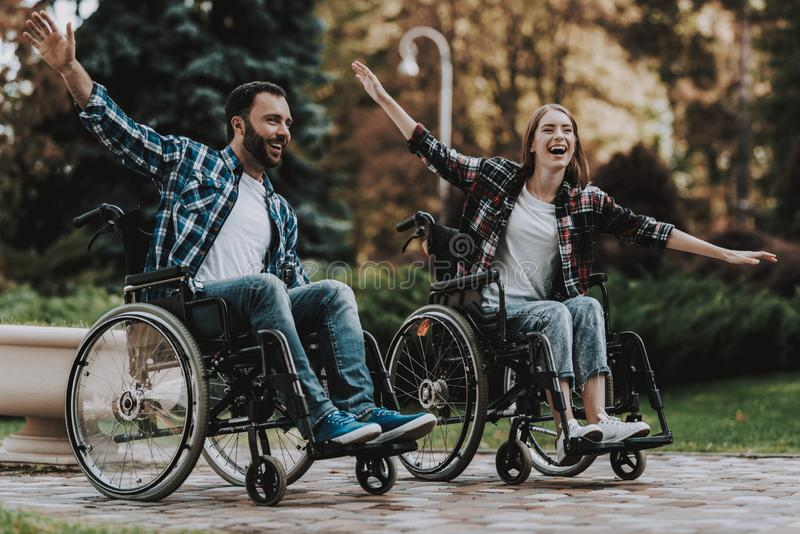 Disabled People on Wheelchairs Have Fun in Park. Disabled Young Man. Woman on Wheelchair. Relaxing in Summer Park. Fun in Summer Park. Recovery and Healthcare royalty free stock photos