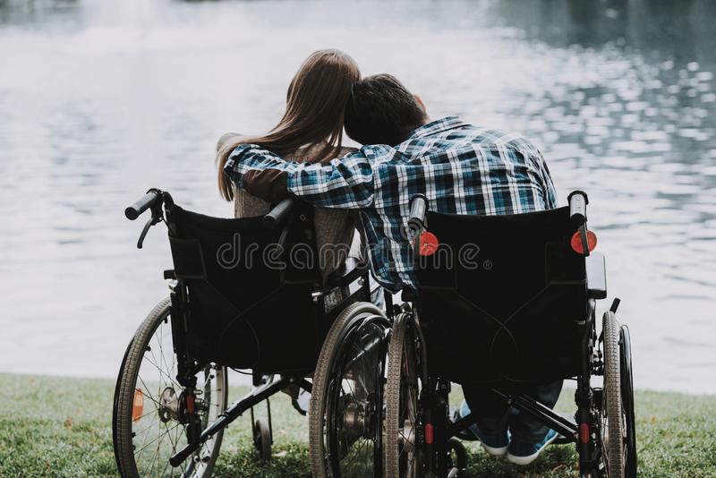 Disabled People on Wheelchairs near Lake in Park. Disabled Young Man. Woman on Wheelchair. Relaxing in Summer Park. Fun in Summer Park. Recovery and Healthcare royalty free stock photos