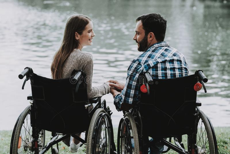 Disabled People on Wheelchairs near Lake in Park. Disabled Young Man. Woman on Wheelchair. Relaxing in Summer Park. Fun in Summer Park. Recovery and Healthcare stock photo