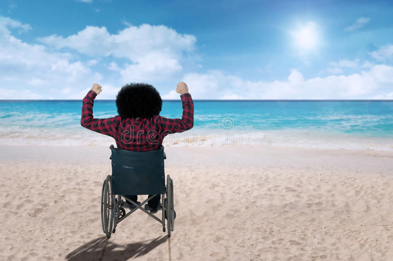 Disabled person in a wheelchair at beach stock photos