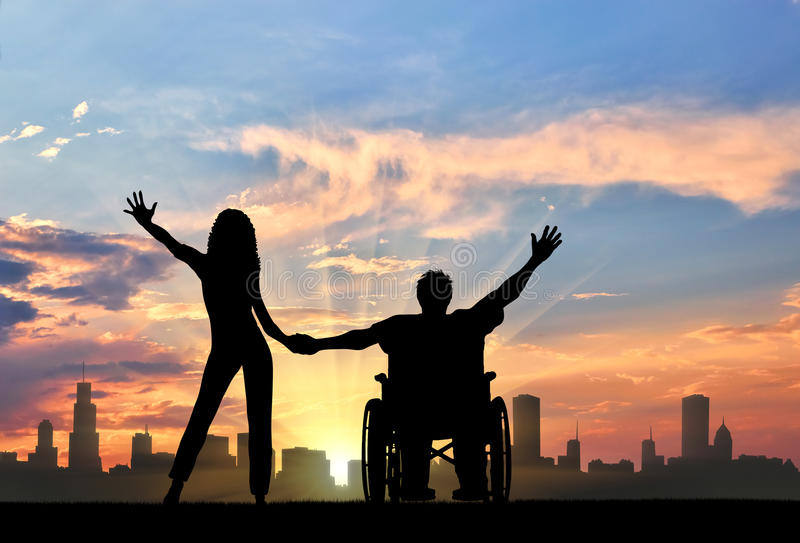 Disabled person in wheelchair with girlfriend on background of city stock image