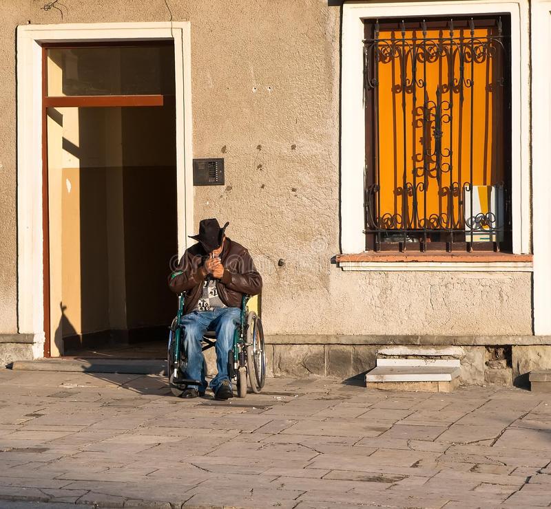 Disabled Person In A Wheelchair Lights A Cigarette Editorial Photo