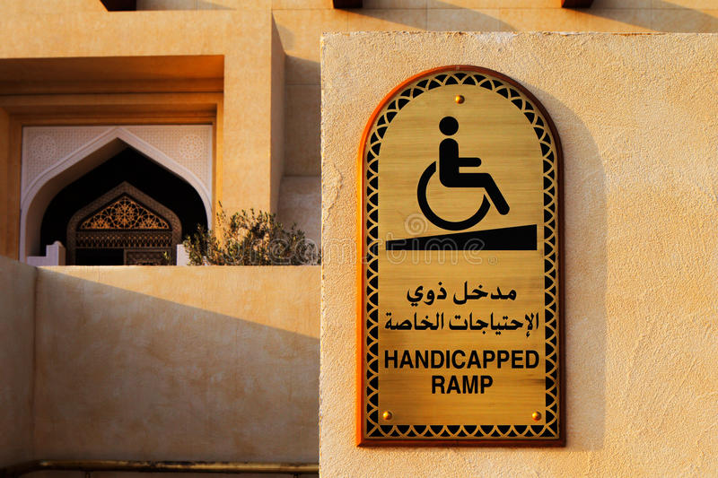 A disabled plaque in Arabic and English at the entrance to the Mosque stock photo