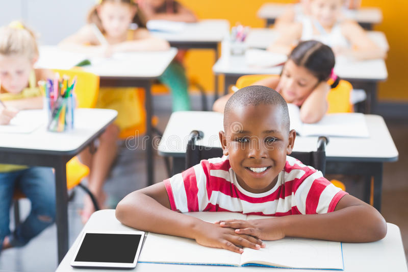Disabled schoolboy smiling in classroom royalty free stock images