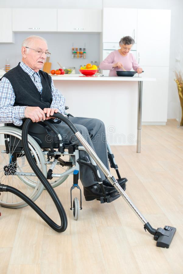 Disabled senior man cleaning while wife cooking royalty free stock photos