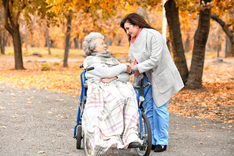 Disabled senior woman and young caregiver. Disabled senior women and young caregiver in park royalty free stock image