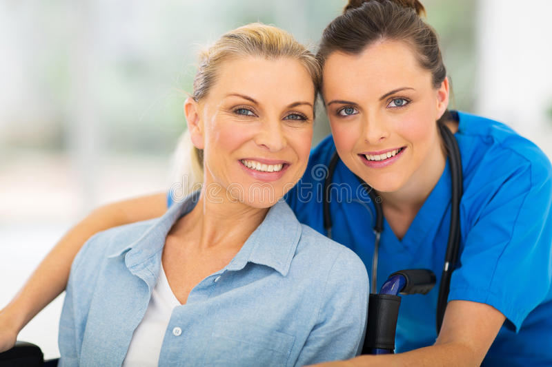Disabled woman caregiver. Portrait of pretty senior disabled women and her caregiver royalty free stock photography