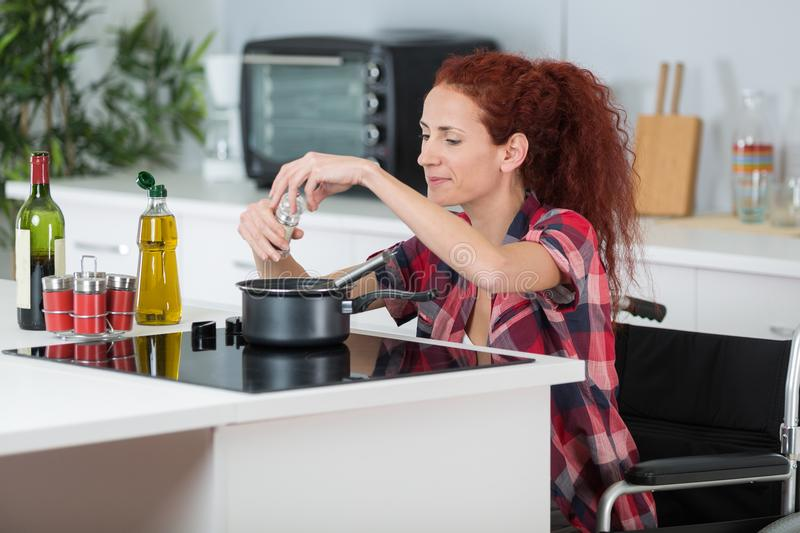 Disabled woman cooking in kitchen royalty free stock photography