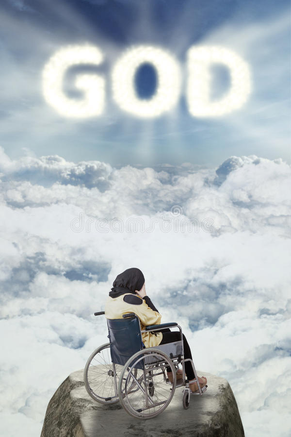 Disabled woman looks sad with god text stock photography