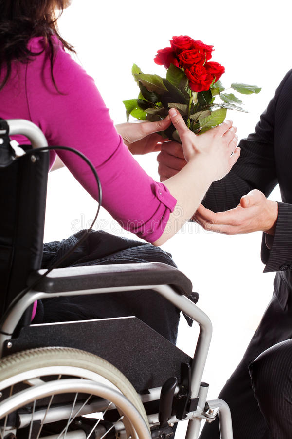 Disabled woman in love. Man proposing to a woman on the wheelchair stock photos