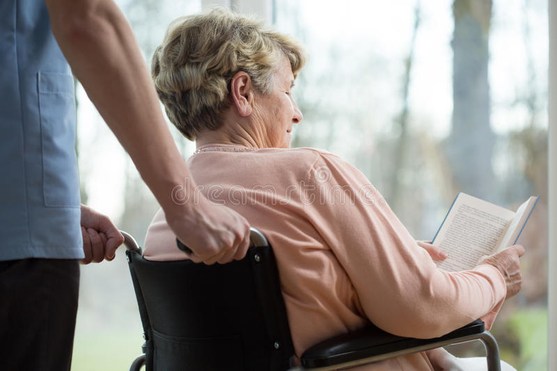 Disabled woman in retirement home. Disabled women reading book in retirement home stock image