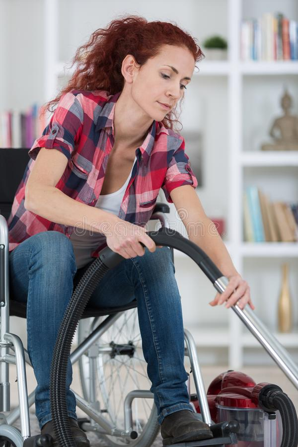 Disabled woman using vacuum cleaner at home stock photo