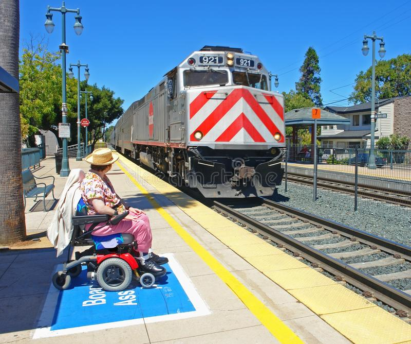 Disabled woman watching her train arrive royalty free stock photography