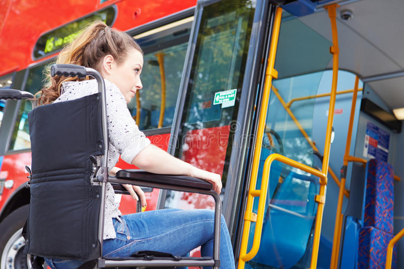 Disabled Woman In Wheelchair Boarding Bus. By Herself Having Difficulty royalty free stock image