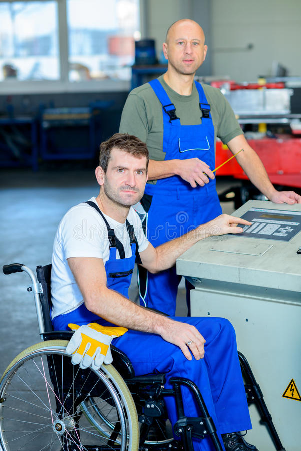 Disabled worker in wheelchair in factory and colleague royalty free stock photos
