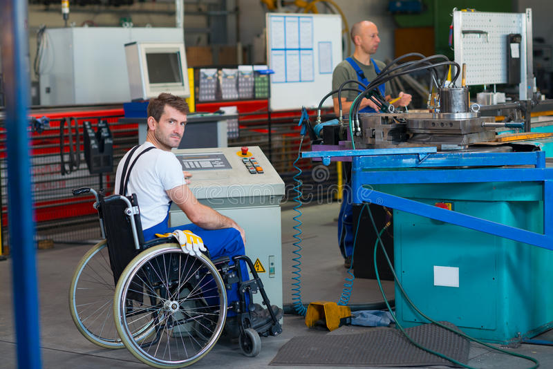 Disabled worker in wheelchair in factory and colleague royalty free stock photo