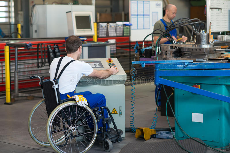 Disabled worker in wheelchair in factory and colleague stock photography