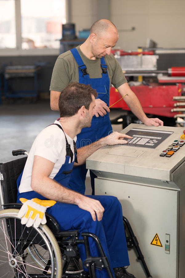 Disabled worker in wheelchair in factory and colleague stock photo