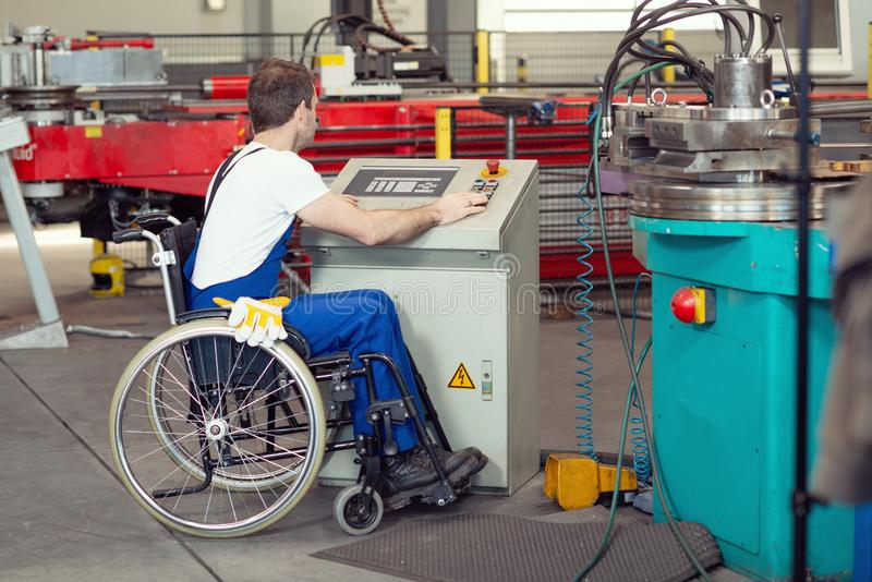 Disabled worker in wheelchair in factory and colleague stock images
