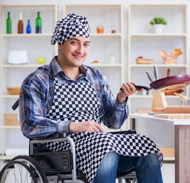 Disabled young husband frying at kitchen. The disabled young husband frying at kitchen stock photos