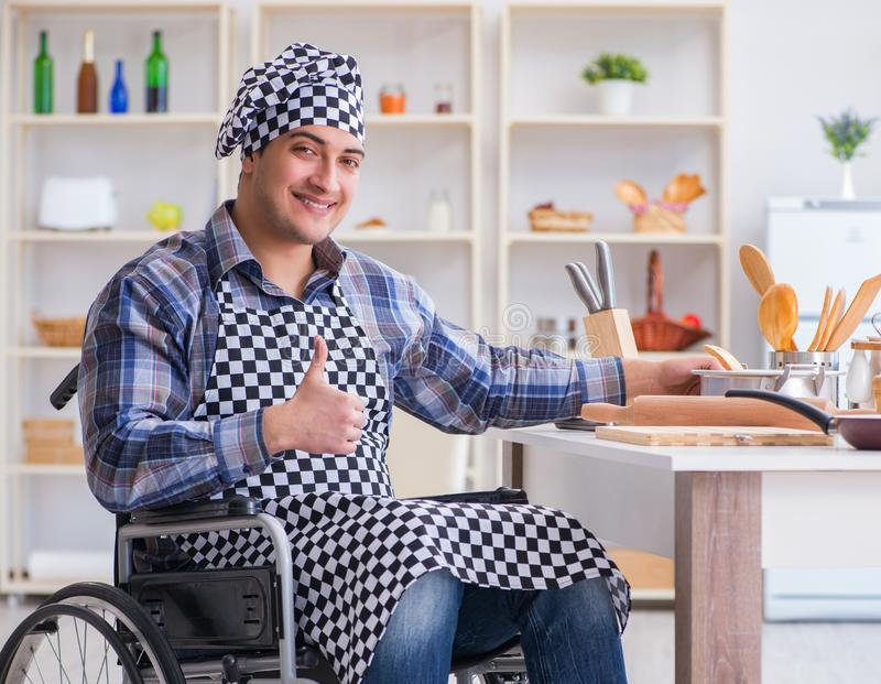 Disabled young man husband working in kitchen stock photography