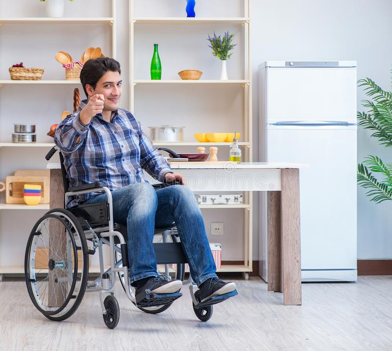 Disabled young man husband working in kitchen royalty free stock photo