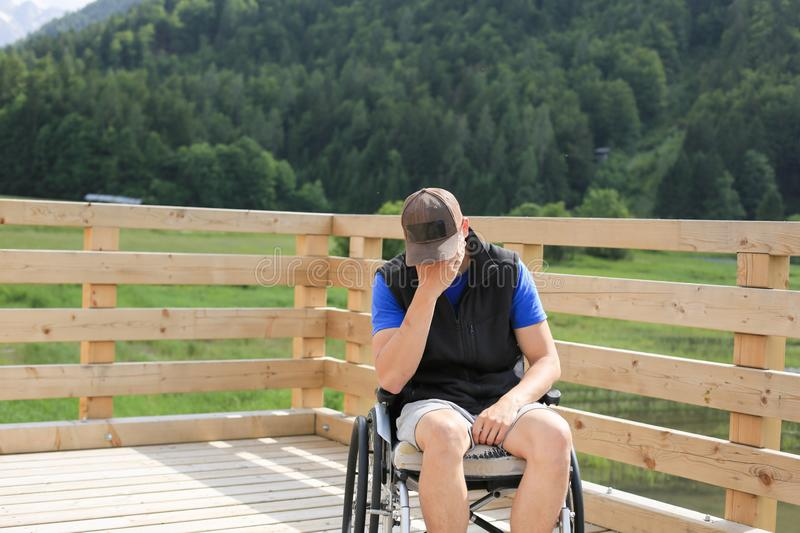 Disabled young man on a wheelchair royalty free stock image