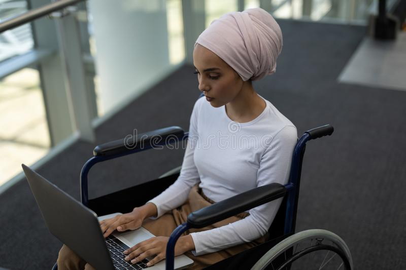 Disabled young mixed-race female executive using laptop in the lobby royalty free stock image