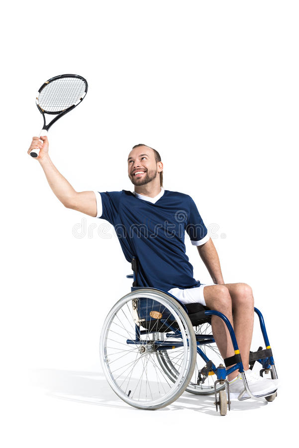 Disabled young sportsman in wheelchair playing tennis and smiling royalty free stock photography