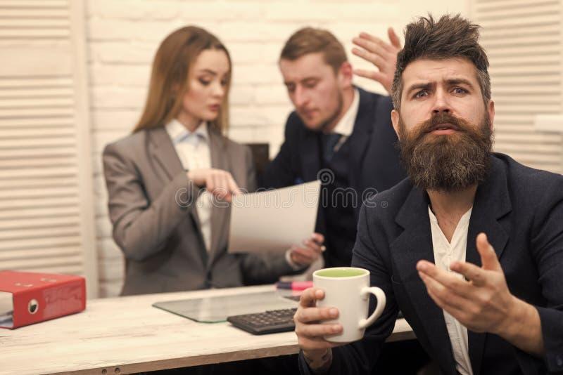 Disaccordi nell'affare L'uomo con la barba sul fronte promettente tiene la tazza, capi, colleghe, colleghi su fondo fotografia stock