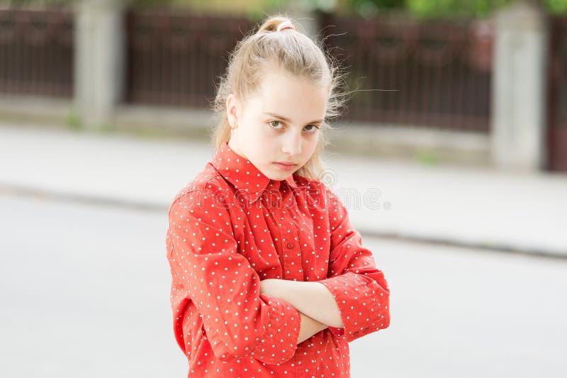 Disaccordo e testardaggine silenziosi di protesta Il fronte serio della ragazza ha attraversato le mani sul bambino del petto inf fotografia stock