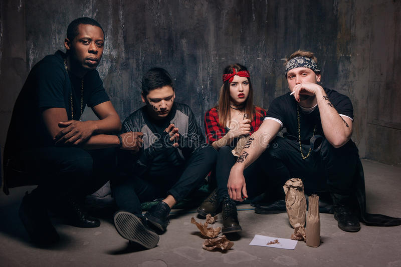 Disadvantaged group of criminal youth with alcohol. Homeless gung members gets drunk. Youth addiction , social problem concept stock photography