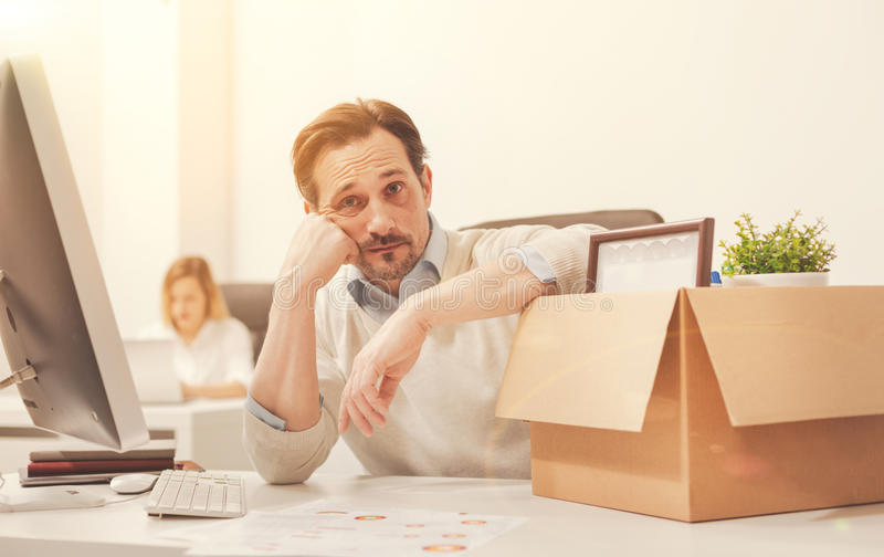 Disanointed young specialist saying goodbye to his job royalty free stock photo